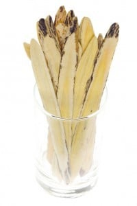 Glass jar containing dried astragalus also known as huang qi in Chinese herbal medicine.